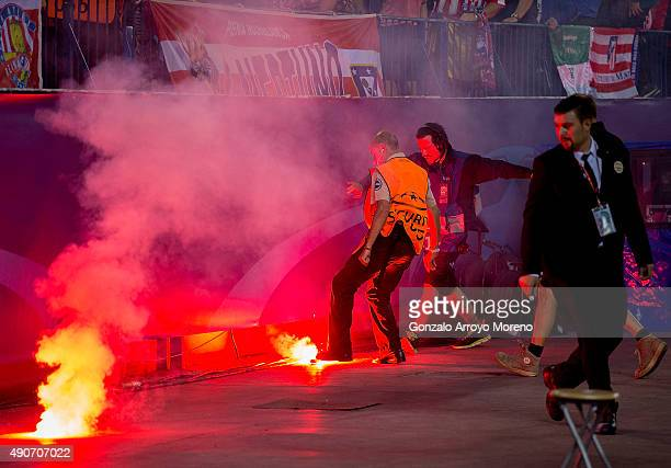 Staff and media tries to extinguish lightflares trown by SL Benfica fans after their team's first goal during the UEFA Champions League Group C match...