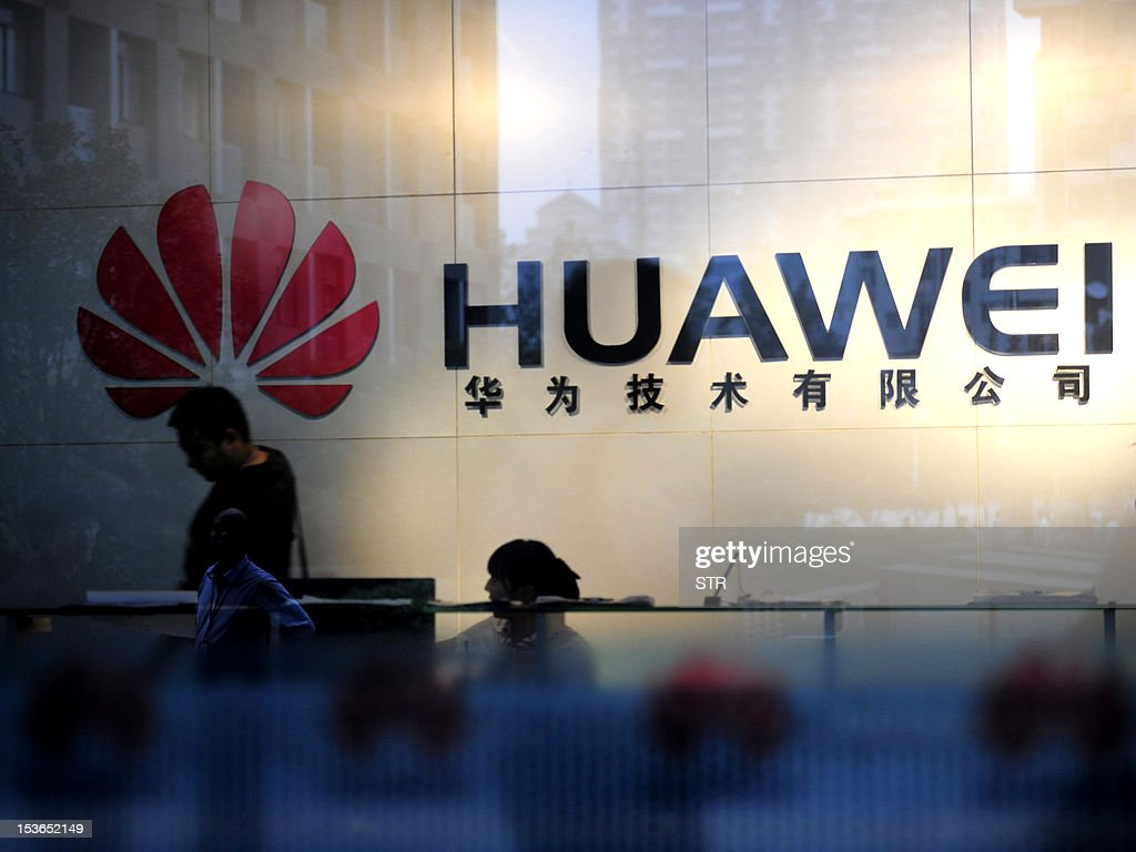 Staff and visitors walk pass the lobby at the Huawei office in Wuhan, central China's Hubei province on October 8, 2012. Beijing on October 8 urged Washington to 'set aside prejudices' after a draft Congressional report said Chinese telecom firms Huawei and ZTE were security threats that should be banned from business in the US. CHINA