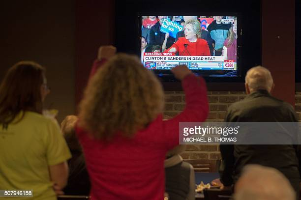 TOPSHOT Staff and volunteers of the Hillary Clinton Burlington Iowa campaign field office cheer as Hillary Clinton speaks on the television at the...