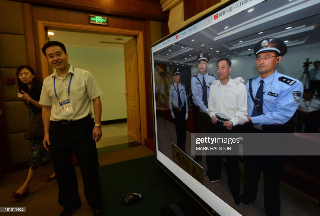 Staff are seen next to an image (R) of disgraced politician Bo Xilai at the Intermediate People's Court after he was sentenced to life in prison after his verdict was announced in Jinan, Shandong Province on September 22, 2013. Fallen Chinese political star Bo Xilai was sentenced by a court to life in prison, following a sensational scandal that culminated in the country's highest-profile trial in decades. AFP PHOTO/Mark RALSTON