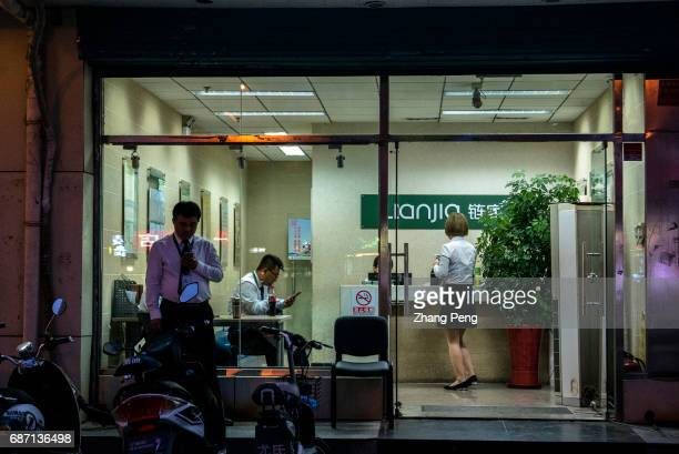 Staff are still working in a Lianjia house agency late at night With the strict regulations by local governments property markets in most Chinese...