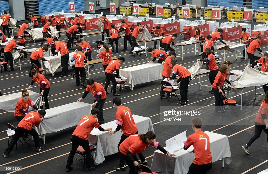 Staff arrange tables during the 7th Wowprime Cup Tray Carrying contest in Taipei on November 5, 2013. Some 1,000 resturants employees and students took part in the event hoping to share in the 8000 USD prize. AFP PHOTO / Sam Yeh