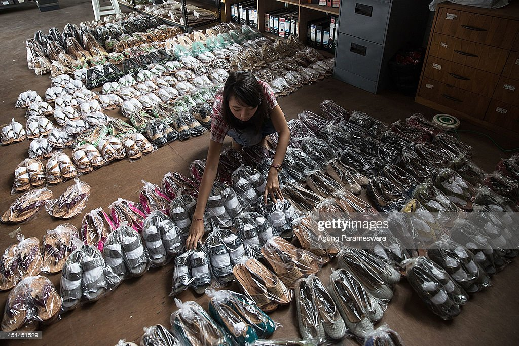 Staff arranges dozen of high heels and sandals that have been wrapped at Niluh Djelantik atelier on November 12, 2013 in Canggu Village, Bali, Indonesia. Niluh Djelantik (formerly called Nilou), the hand made high end leather shoe, is produced by Balinese shoe lover and designer Ni Luh Ayu Pertami with 40 shoes designers and workers in a small atelier at Canggu Village. This brand signature by a unique engraving and designed to be comfortable high heels or wedges with elegan touch. Celebrities like Cate Blanchett, Uma Thurman,Julia Roberts ,Paris Hilton, Cameron Diaz and American top model Gisele Bundchen have been known to purchase Niluh Djelantik beautiful shoes and sandals.