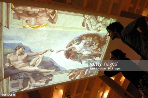 Staff at the British Museum view an illuminated ceiling showing the 'Creation of Adam' by the Renaissance artist Michelangelo at an exhibition called...