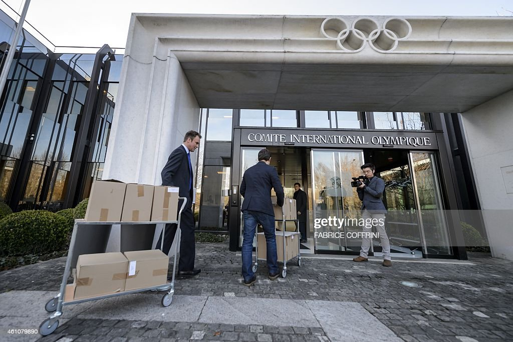 Staff carry the bid files of Almaty on January 6 2015 at the International Olympic Committee headquarters in Lausanne Almaty and Beijing leaders...