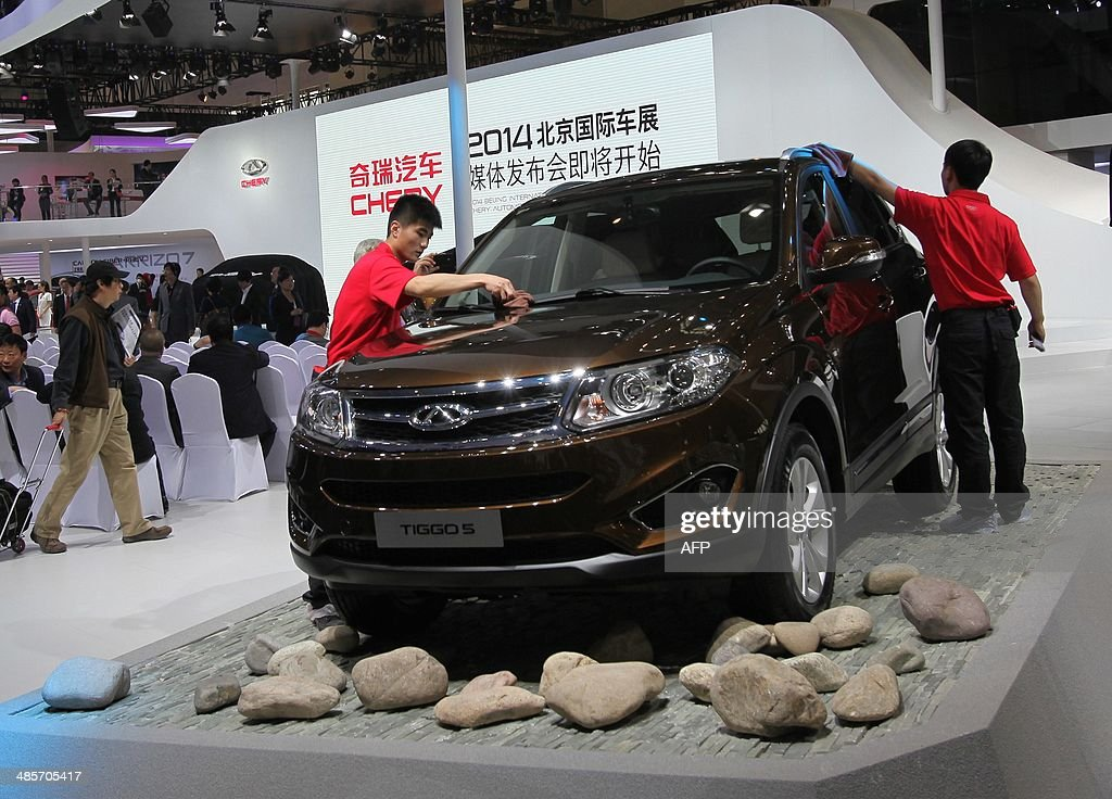 Staff clean a Cherry Tiggo S car at the China International Exhibition Center new venue during the 'Auto China 2014' Beijing International Automotive Exhibition in Beijing on April 20, 2014. Leading automakers are gathering in Beijing for the kickoff of China's biggest car show, but lackluster growth and environmental restrictions in the world's largest car market have thrown uncertainty into the mix. More than 1,100 vehicles are being showcased at the auto show, which opens to the public on April 21. CHINA OUT AFP PHOTO