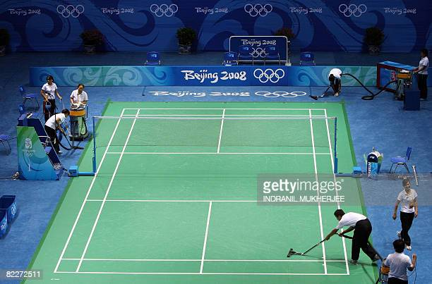 Staff clean the center court at the Beijing University of Technology Gymnasium the venue for badminton matches of the 2008 Beijing Olympic Games in...