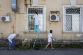 Staff clean windows and remove weeds outside Donetsk morgue on July 23 2014 in Donetsk Ukraine Two Ukrainian military fighter jets were shot down by...