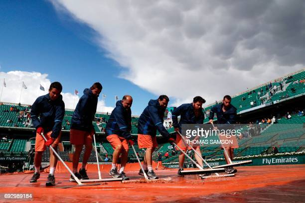 TOPSHOT Staff clear the water from the canvas on the central court after a downpour at the Roland Garros 2017 French tennis Open on June 06 2017 in...