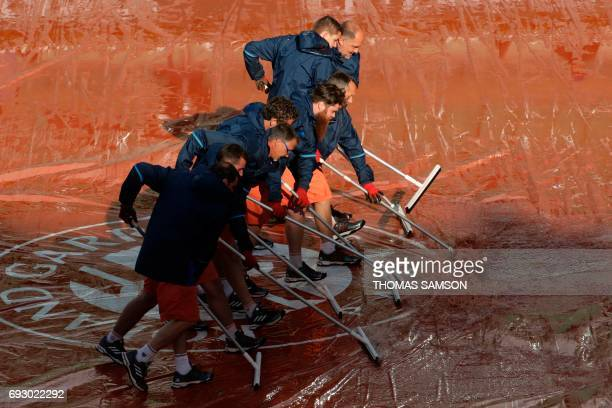 Staff clear the water from the canvas on the central court after a downpour at the Roland Garros 2017 French tennis Open on June 06 2017 in Paris /...