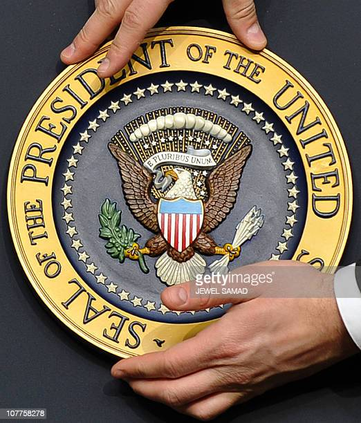 A staff fixes the presidential seal before US President Barack Obama gives a press conference in the Eisenhower Executive Office Building at the...