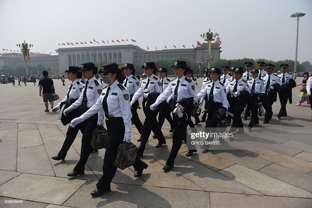 Staff from a security checkpoint march across Beijing's Tiananmen Square on the eve of May Day on April 30, 2016. Millions of people across China are enjoying a three day weekend to mark May Day, on May 1. / AFP / GREG
