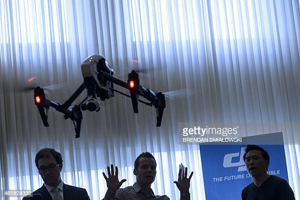 Staff from aerial imaging company DJI demonstrate a remote control aircraft during a press conference by the Small UAV Coalition January 20 2015 in...