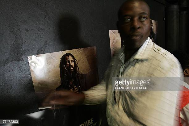 Staff from the Bassline music club in downtown Johannesburg hangs 24 October 2007 posters of South African reggae musician Lucky Dube that was shot...