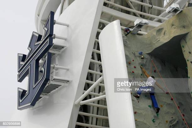Staff get to grips with the climbing wall behind the funnel aboard the Liberty of the Seas the world's newest and largest cruise ship alongside in...