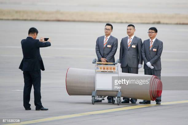 Staff have their picture taken with the carpet they rolled out for the arrival of US President Donald Trump and first lady Melania at Beijing airport...