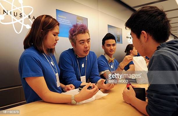 Staff help a customer purchase a new iPhone inside Apple's flagship store in Sydney's central business district on September 20 2013 Sydney was one...