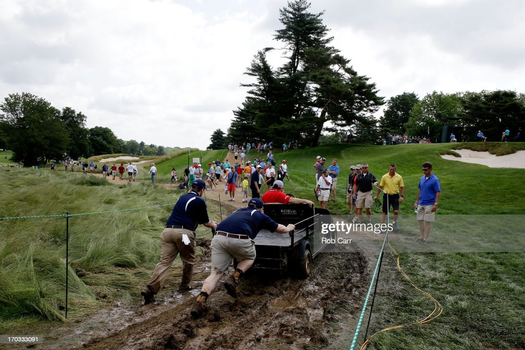 Staff help push a golf cart through the mud during a practice round prior to the start of the 113th U.S. Open at Merion Golf Club on June 11, 2013 in Ardmore, Pennsylvania.