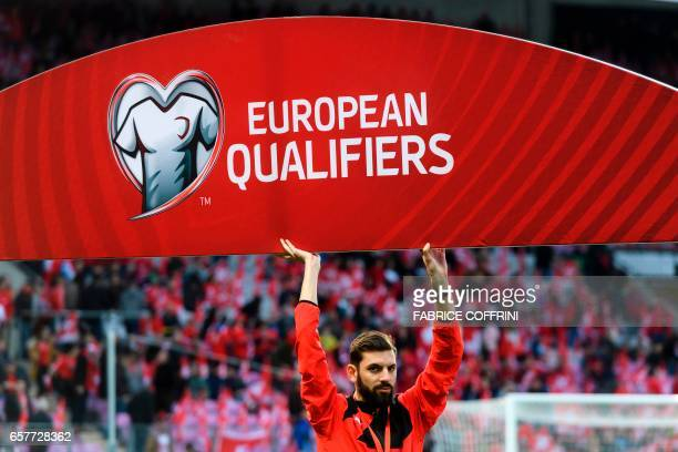 A staff holds a European Qualifiers board prior to the WC 2018 qualifying football match Switzerland vs Latvia on March 25 2017 at the Stade de...
