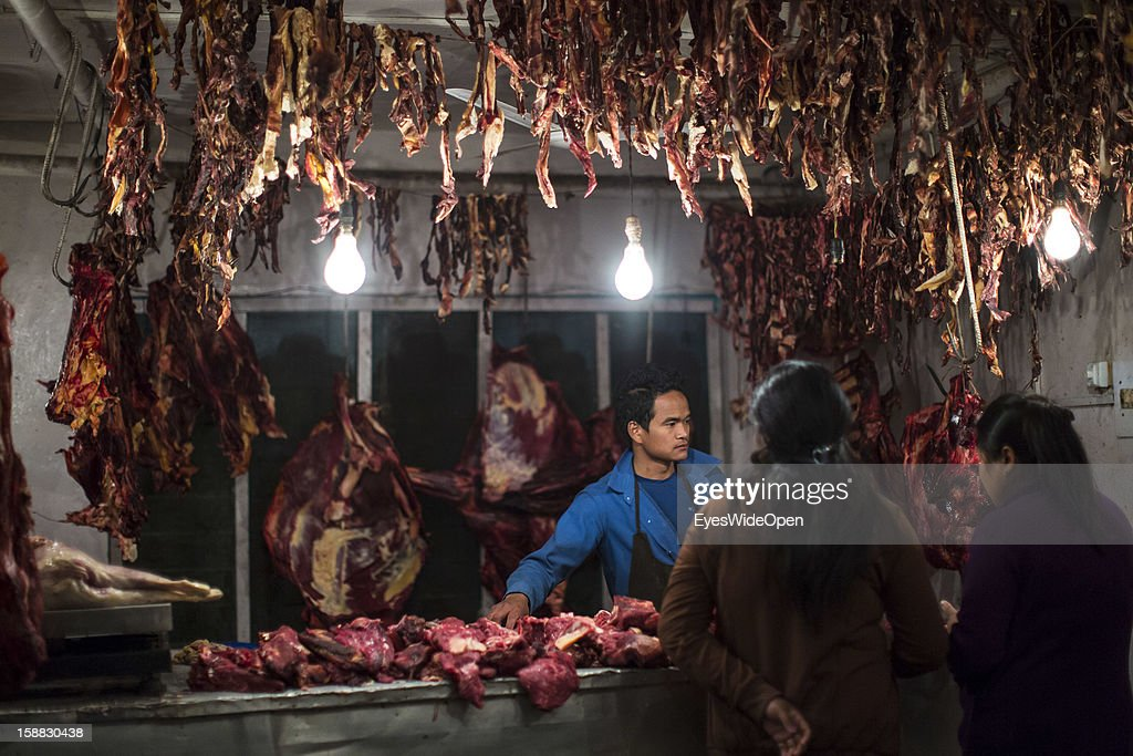 Staff in a butcher ´s shop is selling meat to customer on November 18, 2012 in Thimphu, Bhutan.