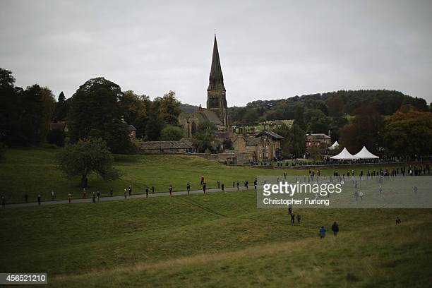 Staff line the route as they await the funeral cortege of Deborah Dowager Duchess of Devonshire at St Peters Church Edensor on October 2 2014 in...