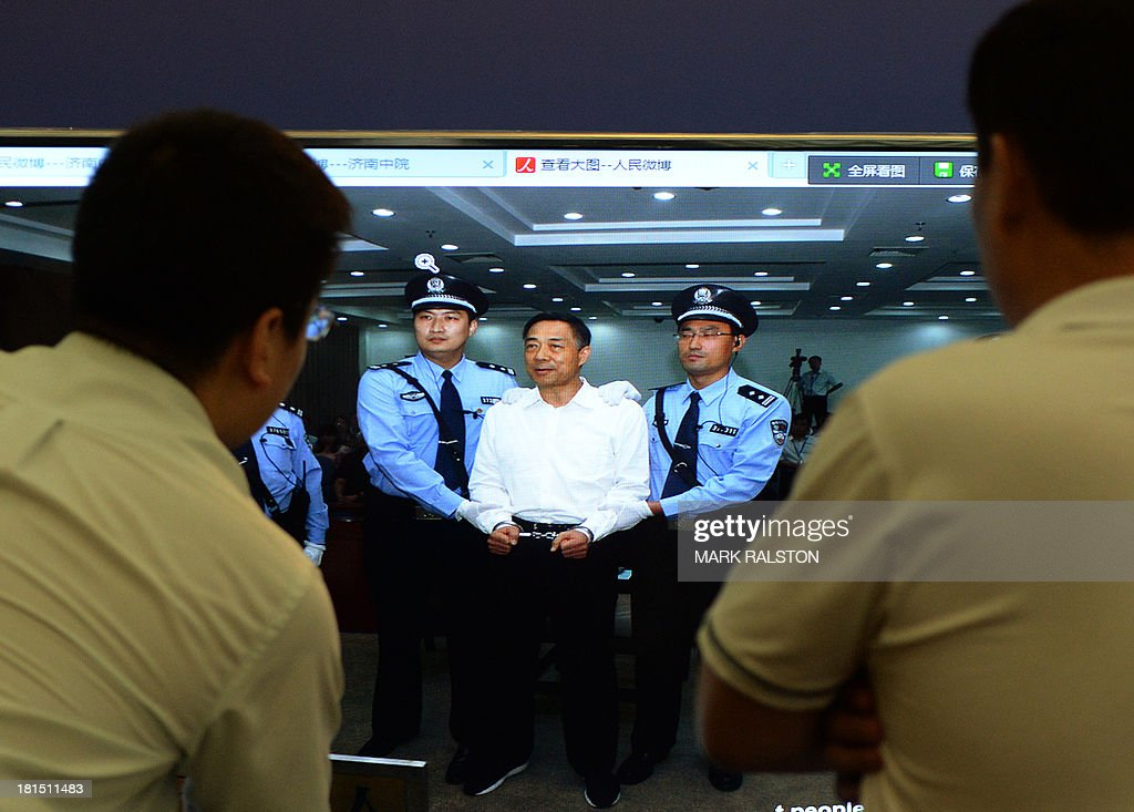 Staff look at an image of disgraced politician Bo Xilai at the Intermediate People's Court after being sentenced to life in prison when his verdict was announced in Jinan, Shandong Province on September 22, 2013. Fallen Chinese political star Bo Xilai was sentenced by a court to life in prison, following a sensational scandal that culminated in the country's highest-profile trial in decades. AFP PHOTO/Mark RALSTON