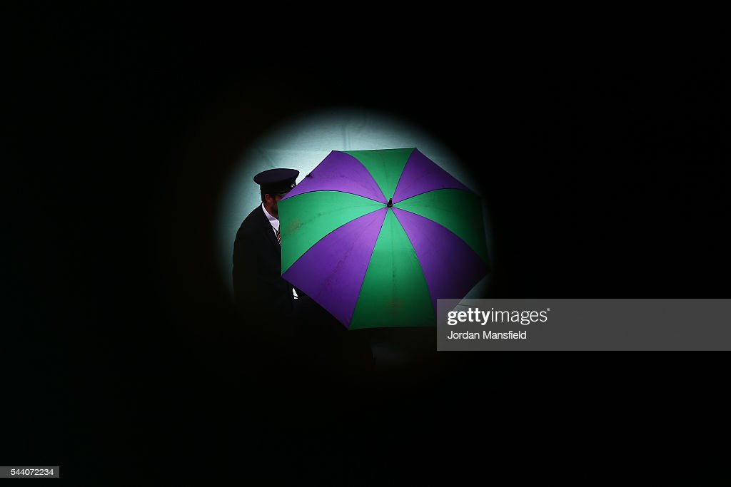 Staff look on from under their umbrellas as the courts are covered on day five of the Wimbledon Lawn Tennis Championships at the All England Lawn Tennis and Croquet Club on July 1, 2016 in London, England.