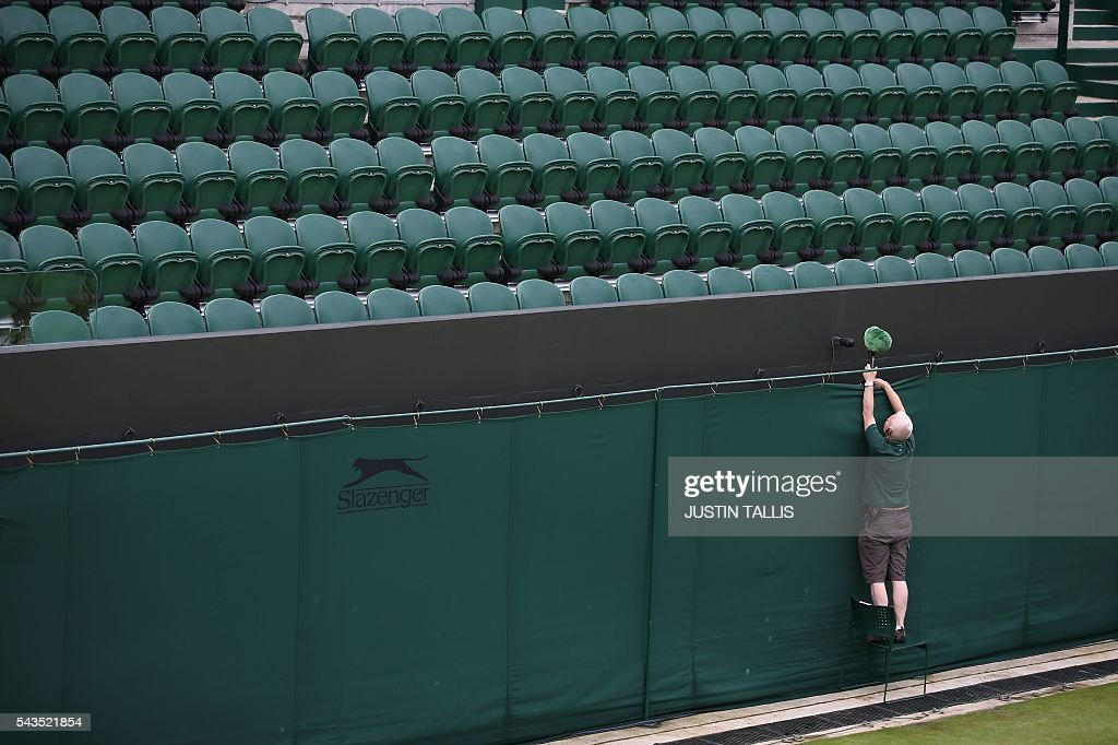 A staff member adjusts the sitting of a microphone on a court before the start of the third day of the 2016 Wimbledon Championships at The All England Lawn Tennis Club in Wimbledon, southwest London, on June 29, 2016. / AFP / JUSTIN