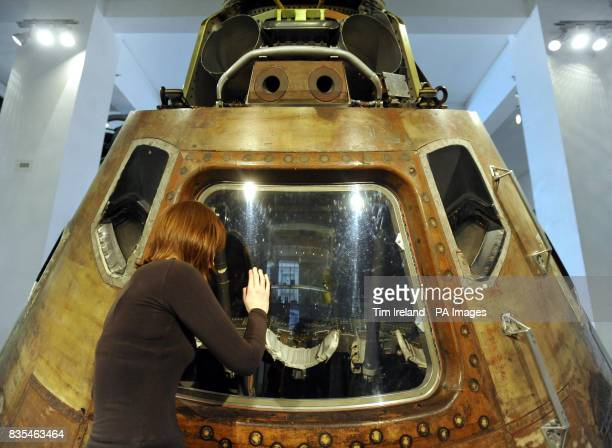 A staff member at the Science Museum in London looks inside the Apollo 10 command module through the perspex cover which will be removed on Saturday...
