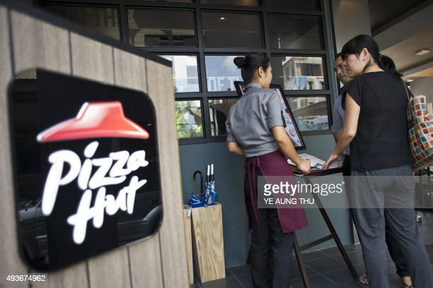A staff member attends to customers browsing the menu of Pizza Hut's first restaurant in Yangon on October 22 2015 Pizza Hut is to open its first...