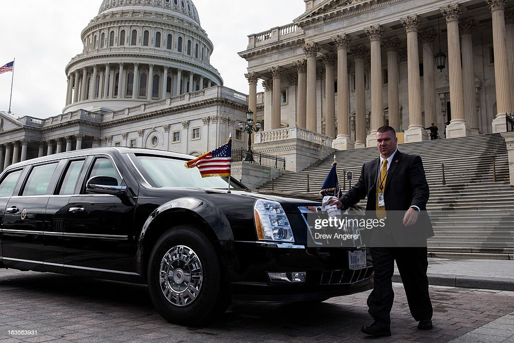 A staff member buffs the presidential limousine while it is parked outside the U.S. Capitol March 12, 2013 in Washington, DC. U.S. President Barack Obama met with the Senate Democratic Caucus today, and is making three trips to Capitol Hill this week to meet with lawmakers.