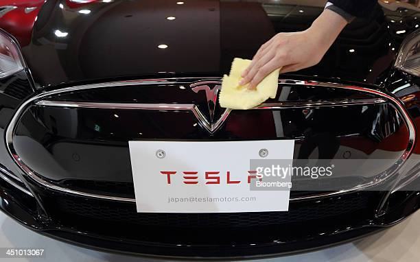 A staff member cleans the Tesla Motors Inc logo on the company's Model S electric vehicle displayed at the 43rd Tokyo Motor Show 2013 in Tokyo Japan...