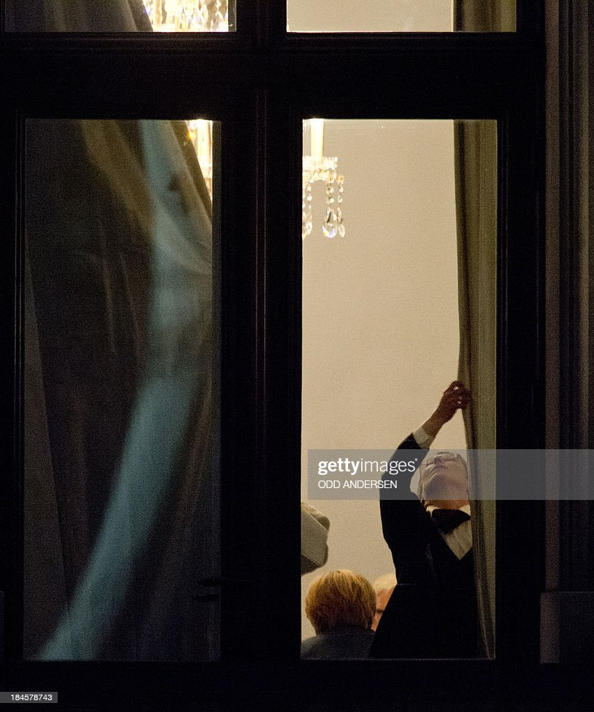 A staff member closes the curtains as German Chancellor Angela Merkel sits in a meeting with her party colleagues and possible coalition partner SPD at the Jakob Kaisers haus at the German parliament during the 2nd round of exploratory talks on forming a coalition government in Berlin on October 14, 2013. The exploratory talks with the left-leaning ecologist party are part of Merkel's hunt for a governing partner after her conservatives won September 22 elections but fell short of a ruling majority.