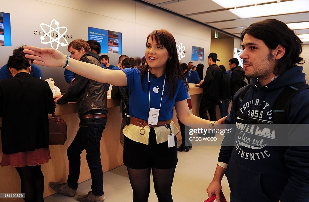 A staff member (C) directs a customer (R) to the sales desk to purchase a new iPhone inside Apple's flagship store in Sydney's central business district on September 20, 2013. Sydney was one of the first places in the world where die-hard Apple fans could get their hands on the new the new iPhone 5s and 5c models. AFP PHOTO / Greg WOOD