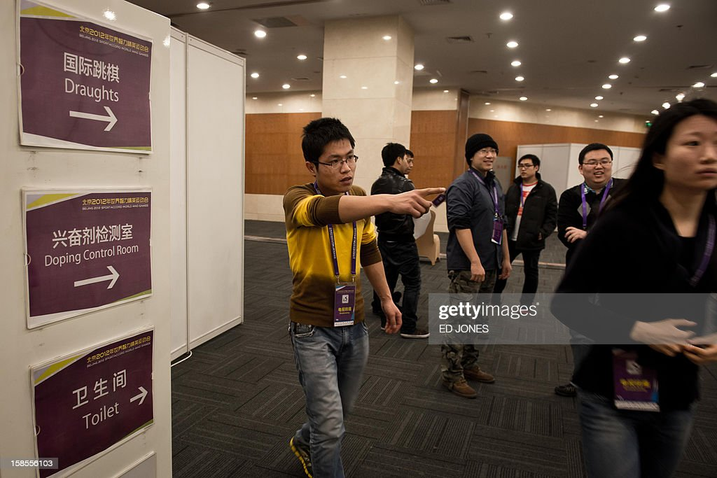 A staff member directs viewers to the venue of a 'blinfold' chess tournament at the Beijing 2012 World Mind Games Tournament in Beijing on December 19, 2012. Some of the world's top chess players went eye-to-eye in the year's highest-level 'blindfold' chess tournament -- seen by some as the toughest challenge in the game. Unable to physically see their own or their opponent's past moves, the players summoned headache-inducing levels of concentration to fight for gold in a silent conference room, lined up in front of laptop screens showing a blank board. AFP PHOTO/ Ed Jones