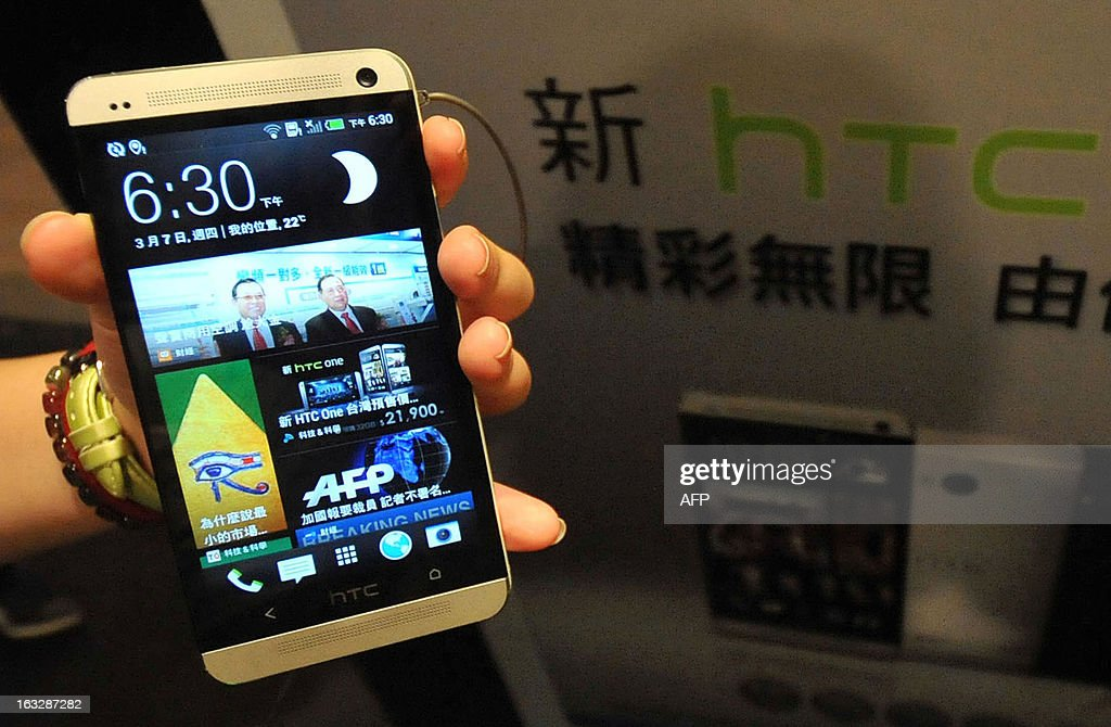 A staff member displays Taiwanese smartphone maker HTC's new 'HTC One' during a press conference in Taipei on March 7, 2013. AFP PHOTO / Mandy CHENG