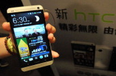 A staff member displays Taiwanese smartphone maker HTC's new 'HTC One' during a press conference in Taipei on March 7 2013 AFP PHOTO / Mandy CHENG