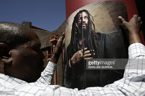 Staff member from the Bassline music club hangs posters 24 October 2007 ahead of the memorial service for South African reggae musician Lucky Dube...