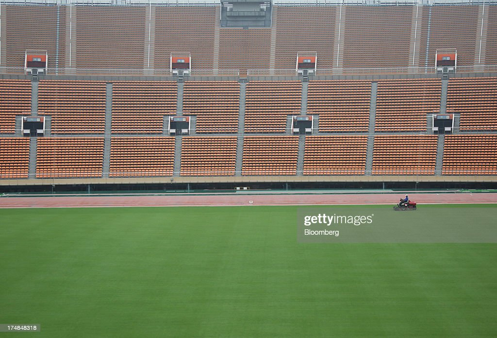 A staff member grooms the pitch of the existing National Olympic Stadium built for the 1964 Olympic games, which will be demolished to make way for a new venue designed by architect Zaha Hadid, during a media tour for Japan's bid for the 2020 Olympic and Paralympic Games in Tokyo, Japan, on Monday, Juy 29, 2013. Tokyo, the front-runner city to host the 2020 Olympics, is planning its biggest housing complex in 42 years to lodge athletes, a move that could benefit developers such as Shimizu Corp. and Mitsubishi Estate Co. Photographer: Tomohiro Ohsumi/Bloomberg via Getty Images