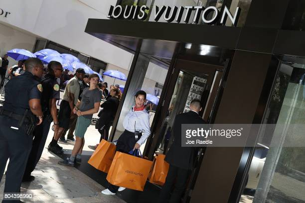 A staff member helps a customer with his bags as people flock to the Louis Vuitton store to purchase limited edition supreme and Louis Vuitton...