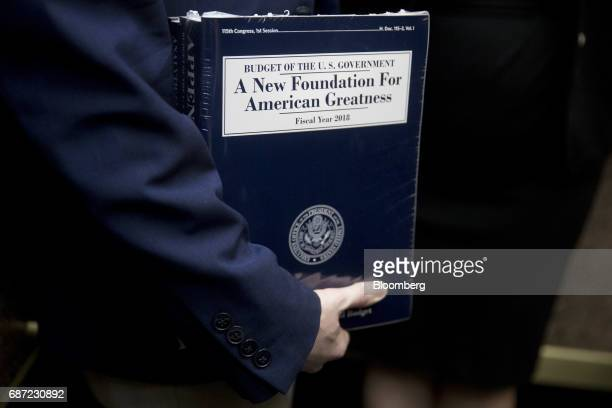 A staff member holds a copy of US President Donald Trump's fiscal 2018 budget proposal on an elevator on Capitol Hill in Washington DC US on Tuesday...