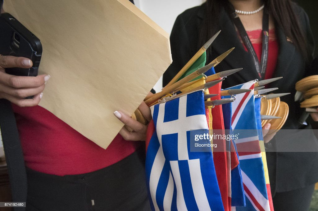 A staff member holds European Union (EU) member flags after a meeting with Jorge Arreaza, Venezuela's minister of foreign affairs, not pictured, and the diplomatic corps at the Yellow House (Casa Amarilla) in Caracas, Venezuela, on Tuesday, Nov. 14, 2017. On November 13, EU nations decided to adopt targeted sanctions against Venezuela, including an 'embargo on arms and on related material that might be used for internal repression.' Photographer: Carlos Becerra/Bloomberg via Getty Images