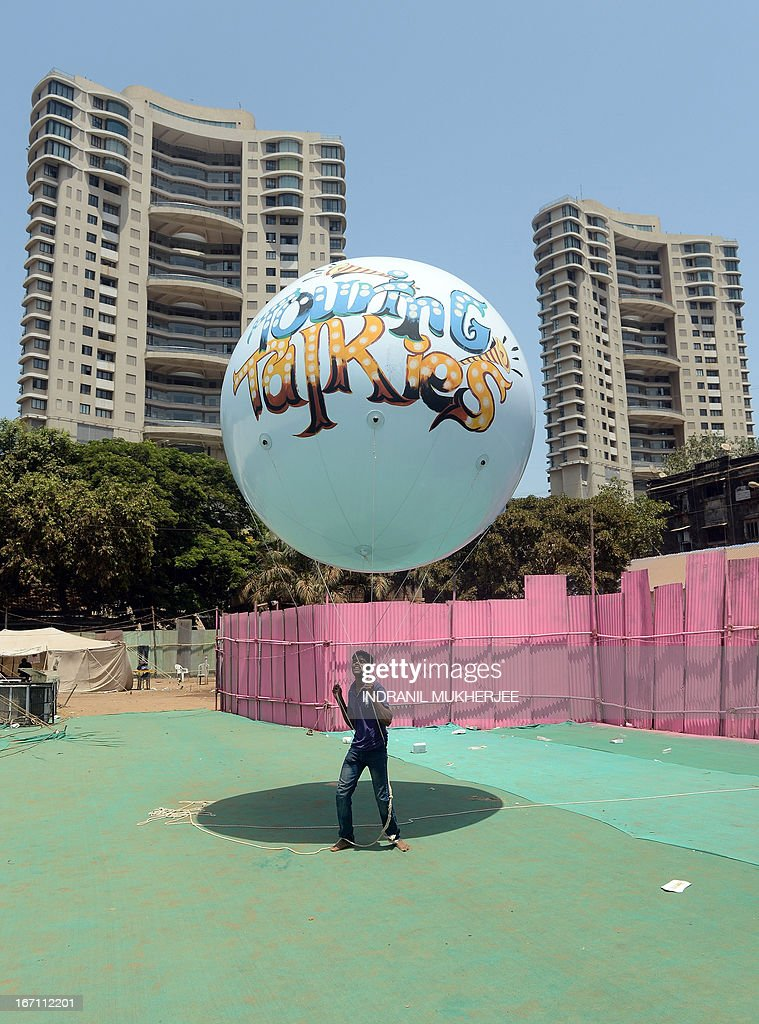 A staff member holds onto a promotional gas-balloon inside the premises of the Anup Touring Talkies tent cinema at a ground in central Mumbai on April 20, 2013. To mark 100 years of Indian Cinema, a Marathi film 'Touring Talkies' is being screened in a makeshift tent theatre just like the days of yore, in its pre-multiplex and pre-single screen glory dating back 50 years. The tents, keeping in mind modern audiences, will have plush seating, air conditioning and popcorn and cola alongside fresh sugar-cane juice, roasted groundnuts and gram and pickle and other tit-bits. The cinema will screen four shows per day for a week. The idea of touring talkies was the brainchild of the doyne of Indian cinema, Dadasaheb Phalke, after he saw the British watching movies in tents. The touring cinema would travel through rural India and screen movies in makeshifts tents. At present, one can only find these talkies - whose sweltering tents and basic facilities contrast with the plush, air-conditioned multiplexes springing up in Indian cities, during Jatras (village fairs) in the interiors of the state.
