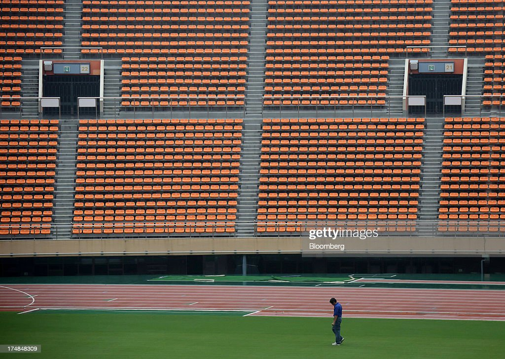 A staff member inspects the pitch of the existing National Olympic Stadium built for the 1964 Olympic games, which will be demolished to make way for a new venue designed by architect Zaha Hadid, during a media tour for Japan's bid for the 2020 Olympic and Paralympic Games in Tokyo, Japan, on Monday, Juy 29, 2013. Tokyo, the front-runner city to host the 2020 Olympics, is planning its biggest housing complex in 42 years to lodge athletes, a move that could benefit developers such as Shimizu Corp. and Mitsubishi Estate Co. Photographer: Tomohiro Ohsumi/Bloomberg via Getty Images