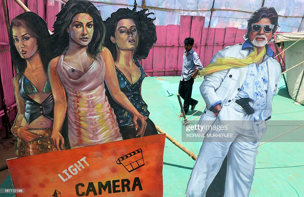 A staff member is seen through a gap in life-size cut-outs of Bollywood stars as he walks inside the premises of the Anup Touring Talkies tent cinema at a ground in central Mumbai on April 20, 2013. To mark 100 years of Indian Cinema, a Marathi film 'Touring Talkies' is being screened in a makeshift tent theatre just like the days of yore, in its pre-multiplex and pre-single screen glory dating back 50 years. The tents, keeping in mind modern audiences, will have plush seating, air conditioning and popcorn and cola alongside fresh sugar-cane juice, roasted groundnuts and gram and pickle and other tit-bits. The cinema will screen four shows per day for a week. The idea of touring talkies was the brainchild of the doyne of Indian cinema, Dadasaheb Phalke, after he saw the British watching movies in tents. The touring cinema would travel through rural India and screen movies in makeshifts tents. At present, one can only find these talkies - whose sweltering tents and basic facilities contrast with the plush, air-conditioned multiplexes springing up in Indian cities, during Jatras (village fairs) in the interiors of the state.