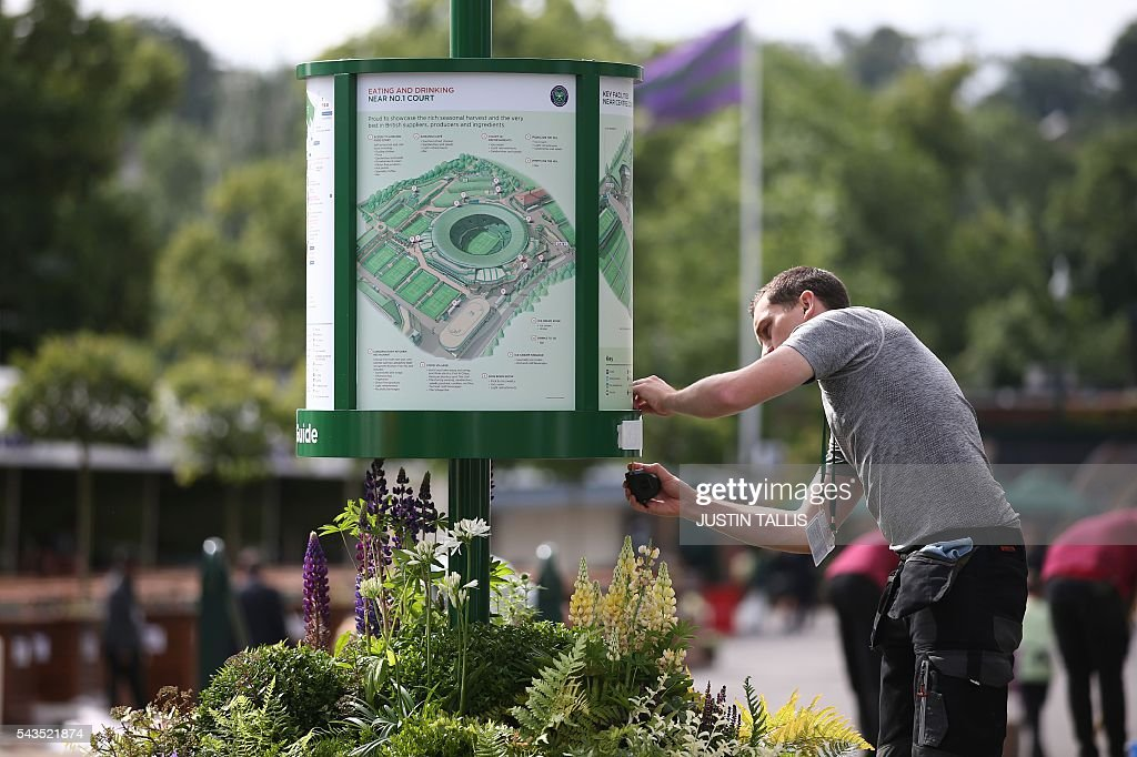 A staff member makes adjustments to an information board before the start of the third day of the 2016 Wimbledon Championships at The All England Lawn Tennis Club in Wimbledon, southwest London, on June 29, 2016. / AFP / JUSTIN