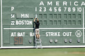 A staff member manually changes the scoreboard during a spring training game between the Boston Red Sox and the Minnesota Twins at JetBlue Park on...