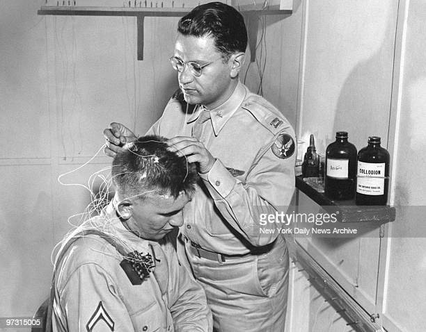 Staff member of Department of Research Neuropsychiatry at the School of Aviation Medicine Randolph Field examines electrodes on Army aviation cadet...