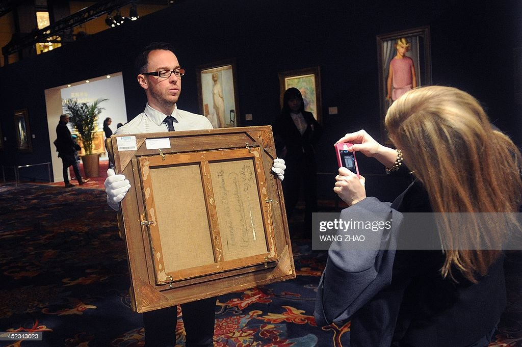 A staff member (L) of Sotheby's shows the back of a painting as a woman (R) takes a photo at Sotheby's exhibition in Beijing on November 28, 2013. A 50 million USD Rembrandt painting, alongside masterpieces of Picasso Renoir or Rodin, are on sale in Beijing, showing the growing appetite of rich Chinese for Western art.