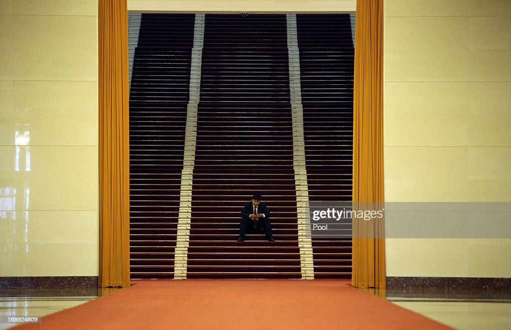 A staff member of the Great Hall of the People checks his mobile as he sits on the steps ahead of a meeting between China's President Xi Jinping and Greece's Prime Minister Antonis Samaras, in Beijing, May 17, 2013. Greece is willing to roll out the 'red carpet' according to Samaras if China was willing to invest in the Greek economy.